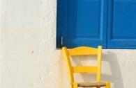 European-Greece-Greek-Island-Mykonos-blue-shutters-yellow-chair.jpg